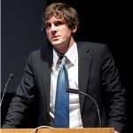Photograph of a young white man wearing a suit and tie, giving a speech at a podium.