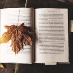 A book is open, and a passage marked with a pencil. A yellow post-it note sticks out the side. One the left-hand page, a large yellowy-brown sycamore leaf is spread out.